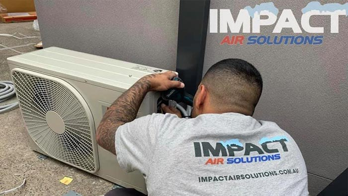 Worker repairing outdoor air conditioning unit.