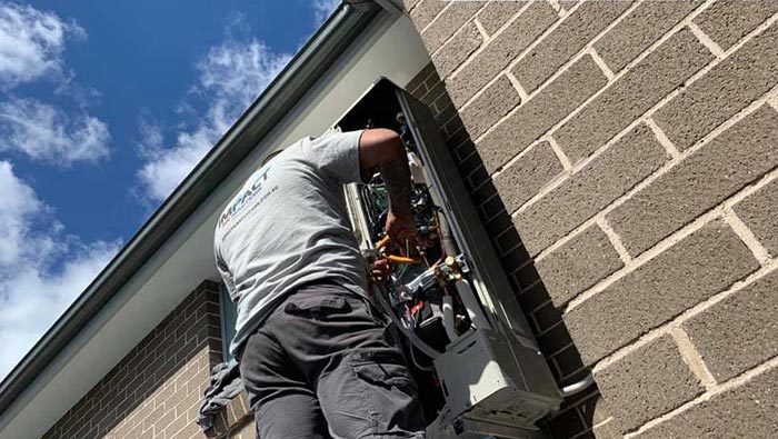 Worker servicing outdoor air conditioning unit.