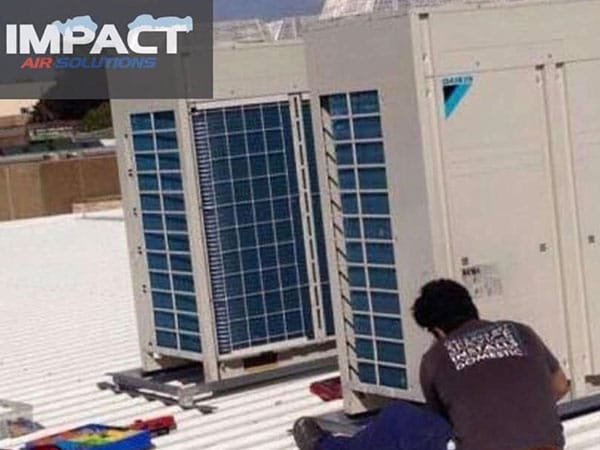 Worker on roof installing commercial HVAC outdoor units
