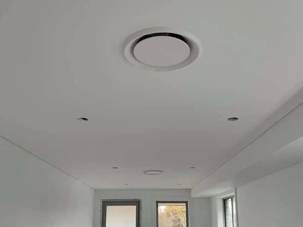 Circular ceiling vents as part of a ducted air conditioning system.