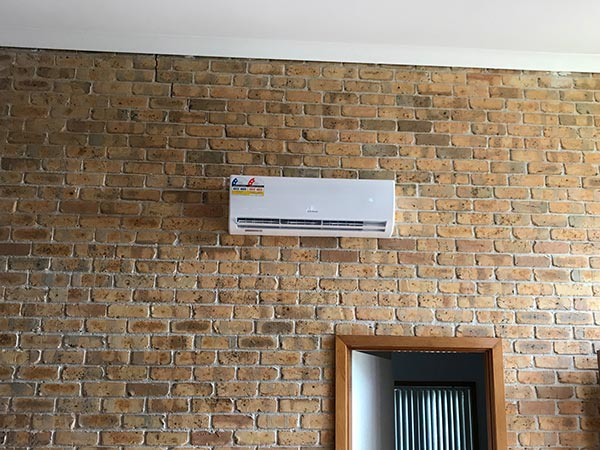 Indoor wall mounted unit attached to a interior brickwall as part of a split system air conditioner.