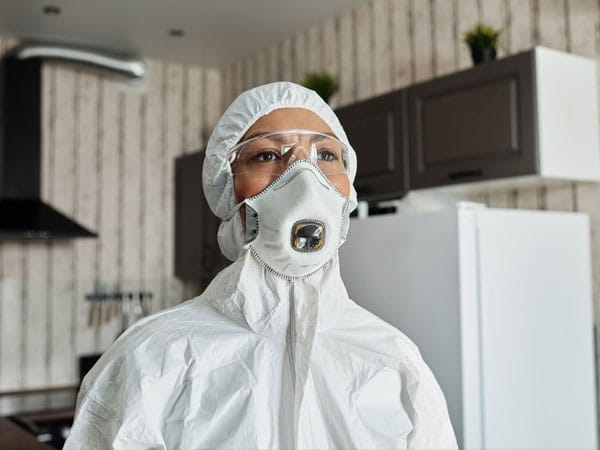 Woman in Protective Suit About to Disinfect a Residential Area