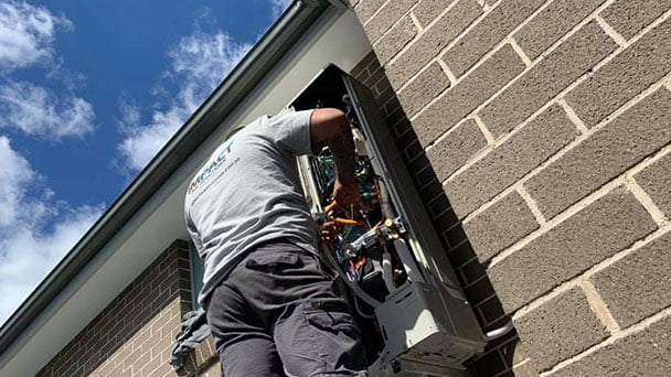 AC technician servicing outdoor air conditioning unit.