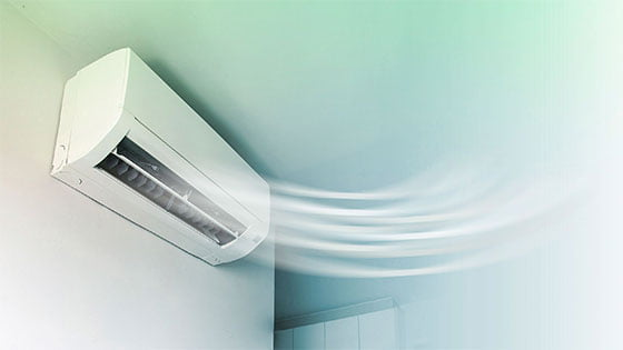 Wall mounted unit of split system blowing cool air indoors